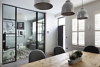 Folding glass door help deliniate the small rooms in this mews house, whilst ensuring light still flows through the space