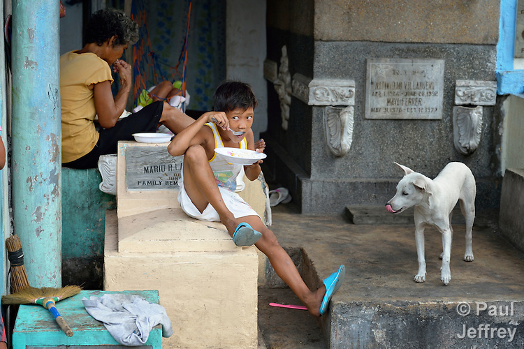 """In the capital of the Philippines, ten-year old Jobert Rio Florido eats with his grandmother Rodelin Carillo in a mausoleum that is their family home in the Manila North Cemetery. Hundreds of poor families live here, dwelling in and between the tombs and mausoleums of the city's wealthy. They are often discriminated against, and many of their children don't go to school because they're too hungry to study and they're often called """"vampires"""" by their classmates. With support from United Methodist Women, KKFI provides classroom education and meals to kids from the cemetery at a nearby United Methodist Church."""