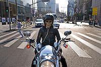 Un motociclista con una maschera fermo ad un incrocio in attesa del semaforo verde.<br /> A biker wearing a mask  in the center
