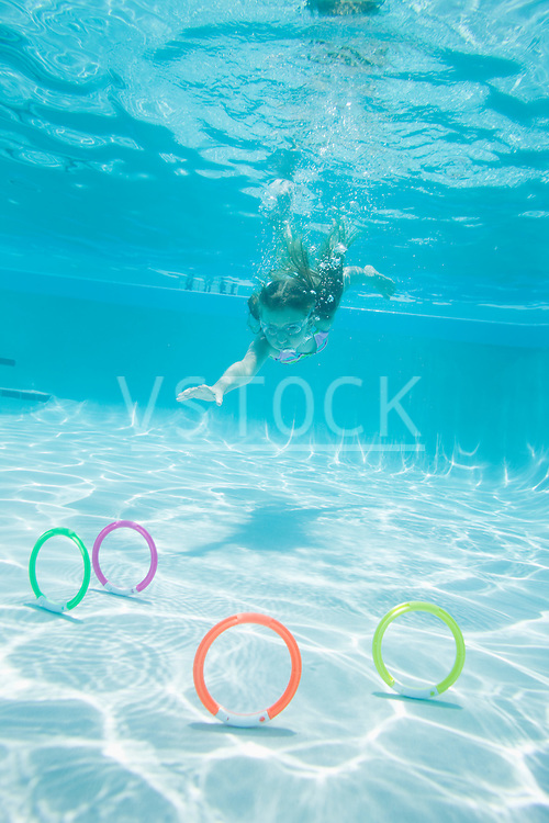 USA Florida, St. Pete Beach, Underwater shot of girl (8-9) diving in swimming pool, colorful circles on floor in foreground