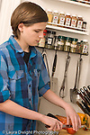 Teenage boy at home in kitchen food preparation slicing tomato vertical Caucasian age 14