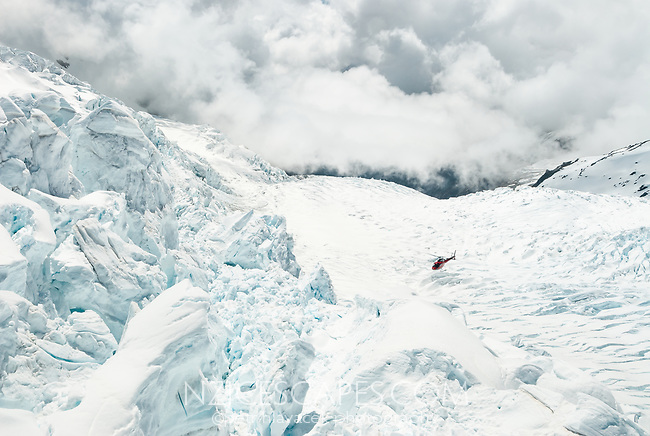 Helicopter flying among seracs and crevasses in upper parts of Franz Josef Glacier icefall, Westland Tai Poutini National Park, UNESCO World Heritage Area, South Westland, West Coast, New Zealand, NZ