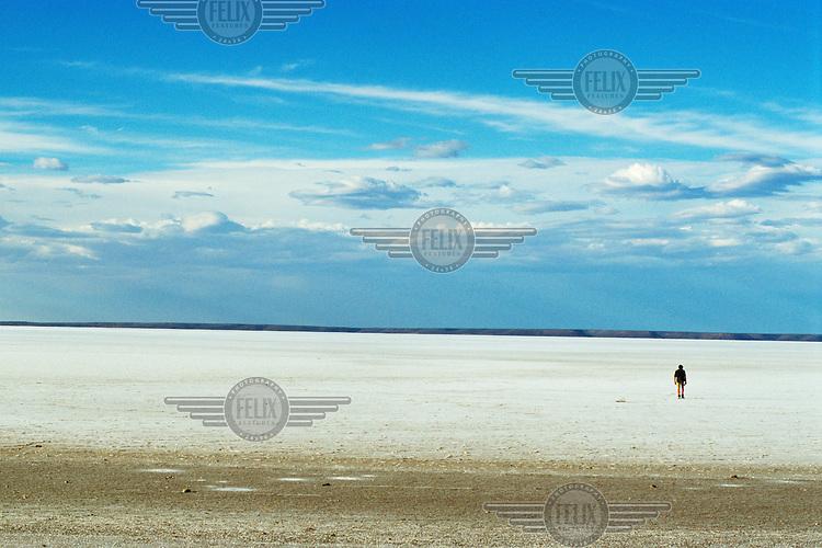 A man walks across Lake Hart, a dry salt lake that occasionally floods.