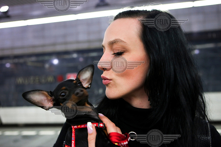 A woman kissing her Chihuahua dog at the Muzeum metro station.