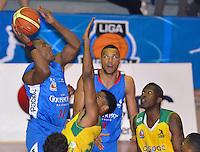 BOGOTÁ -COLOMBIA. 07-06-2014. Norvey Aragon (Izq) de Guerreros de Bogotá trata de anotar una cesta sobre Hunter Randall (C) de Cimarrones del Chocó durante el cuarto partido por los playoffs finales de la  Liga DirecTV de Baloncesto 2014-I de Colombia realizado en el coliseo El Salitre de Bogotá./ Norvey Aragon (L) of Guerreros de Bogotátries to basket over Hunter Randall (C) of Cimarrones del Choco during the 4th game for the playoffs finals of the DirecTV Basketball League 2014-I in Colombia played at El Salitre coliseum in Bogota. Photo: VizzorImage/ Gabriel Aponte / Staff