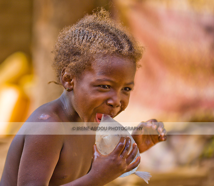 Throughout West Africa, hawkers sell plastic bags filled with ice water for 25 cfa (about five cents!).   Here, in Ouagadougou, Burkina Faso, a young Fulani girl  prepares to bite into a plastic bag filled with the refrigerated water.