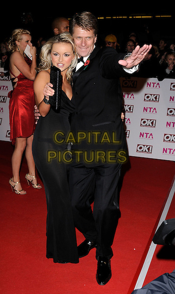 OLA JORDAN & ANDREW CASTLE .Arriving at the National Television Awards held at the Royal Albert Hall, London, England..October 29th, 2008 .NTA red carpet arrivals full length black suit dress clutch bag hand arm .CAP/CAN.©Can Nguyen/Capital Pictures.