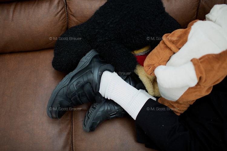 George Eugene Rouse, Jr., 68, naps after lunch in the residences in Malone Park at the Fernald Developmental Center in Waltham, Massachusetts, USA.  Rouse was born without problems but contracted spinal meningitis and was institutionalized in 1951.  Rouse frequently lays with a towel around his neck surrounded by stuffed animals.