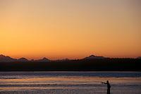Fisherman at sunrise, casting. Point No Point, WA. North Kitsap Peninsula. West side of Puget Sound.