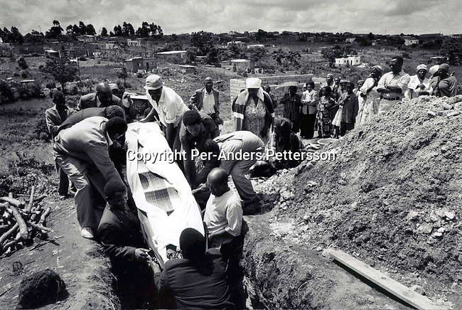 GAMALAKHE, SOUTH AFRICA - SEPTEMBER 13:  Unidentified men lowers a coffin with a woman who died of a Aids related disease on September 13, 1999 in Gamalakhe, in Natal, South Africa. South Coast Hospice, a local hospice that helps people to manage in this rural area, helped them to pay for the funeral. Its estimated that about one thousand South African's are infected a day and that about five million of the population are infected. .Photo: Per-Anders Pettersson/ iAfrika Photos.......A woman who died of Aids related disease is buried on September 13, 1999 in her garden in Gamalakhe, South Africa. South Africa has the highest increae of HIV/Aids in the world and about 8 million people are infected in the country..(Photo: Per-Anders Pettersson/ Liaison Agency)
