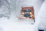 Heavy snowplow plowing suburban neighborhood street during blizzard