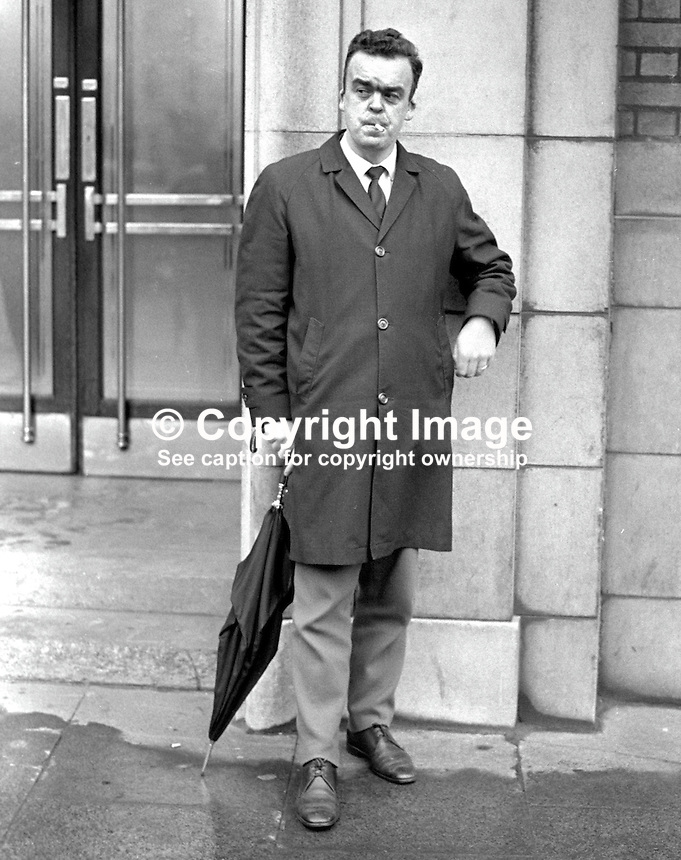 Leo McBrien, RUC, on VIP protection duty waits for Captain Terence O'Neill, Prime Minister, N Ireland, to emerge from BBC Broadcasting House, Belfast, following the recording of his &quot;Ulster stands at the Crossroads&quot; speech. His rank at time of photo not known but he went on to become a Chief Inspector. On 17th October 1971 whilst a Detective Sergeant he survived being shot in the head at point blank range while his vehicle was stopped at traffic lights. 196812090298b.<br />