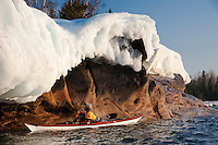 Lake Superior sea kayaker explores icy shoreline in spring on Michigan's Upper Peninsula.