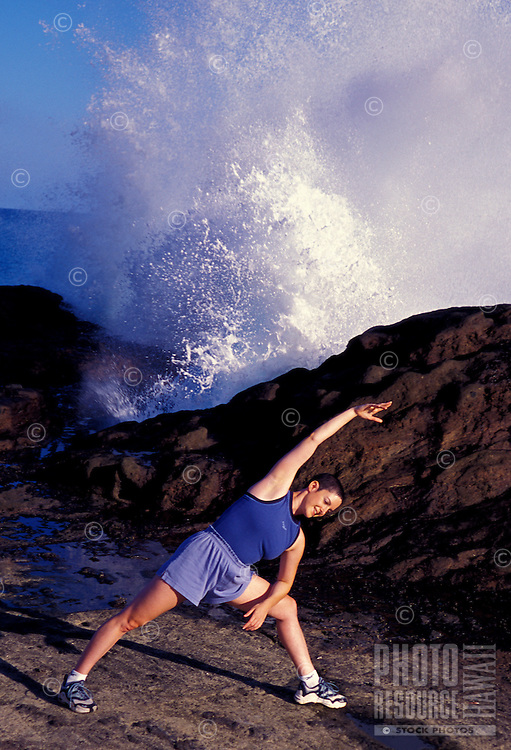 Woman doing yoga stretches near halona blow hole on Oahu's east coast