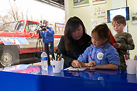 NWA Democrat-Gazette/CHARLIE KAIJO Sunny Park of Los Angeles (from left) colors with Sophia Myers, 8 and Julian Myers, 5, Thursday, March 29, 2018 at The Walmart Museum at Bentonville Square in Bentonville. <br />