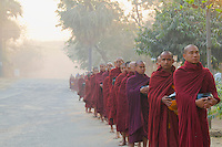 Monks collecting their morning aims in the dust covered street of Bagan, Myanmar/Burma