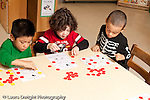 Education preschool 3-4 year olds three boys sitting at table playing bingo game about body parts using colored plastic counters one boy is wearing a skeleton shirt horizontal