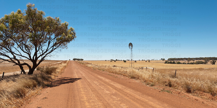 Hot dusty road across flat landscape with water vane