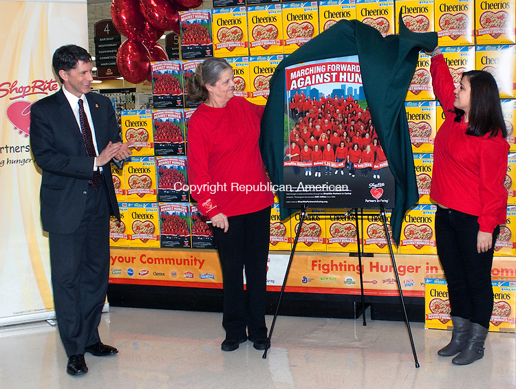 WATERBURY CT-MARCH  12 2013 -03073DA01- Owner of the ShopRite store in Waterbury Paul Tornaquindici  applaud as Shoprite associates, Linda Nightingale of Terryville, center and Anisa Barolli of Waterbury unveil a special edition Cheerio box that the pair will be featured on for their commitment of service to their store during a ShopRite Partners In Caring celebrate.Darlene Douty Republican American