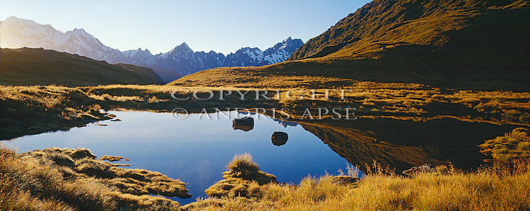 Small tarn on the Copland Range. Southern Alps in background. Westland Region. New Zealand.