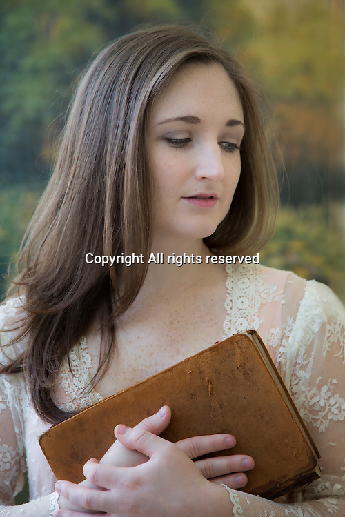 A young lady holds a book.