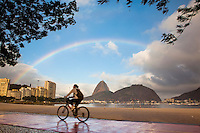 Cyclist rides at Botafogo beach enjoying the view of Sugar Loaf under the rainbow, Rio de Janeiro lifestyle, Brazil.
