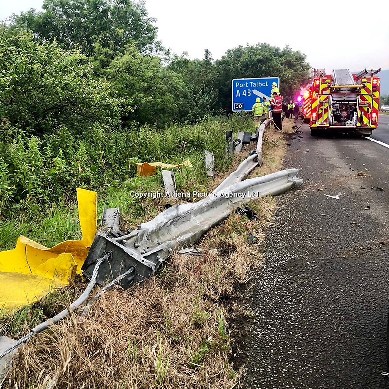 """Pictured: Fire service and police crews attend the scene where a silver car dropped 30ft off the M4 motorway.<br /> Re: A driver came off the M4 motorway before dropping down a 30ft embankment near the Margam Junction in south Wales.<br /> The male driver of the silver car suffered minor injuries despite the car landing on its side between trees and bushes.<br /> South Wales Police tweeted: """"Single vehicle RTC, amazingly driver suffering minor injuries only after dropping off the motorway and down a 30ft embankment.""""<br /> Mid and West Wales Fire and Rescue Service crews attended the scene."""