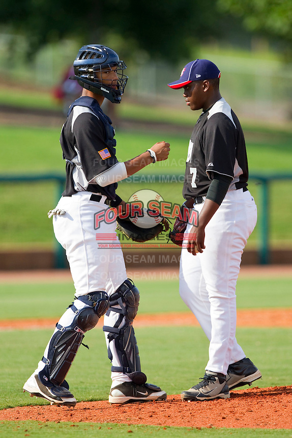 Catcher Blake Hickman #25 of RBI has a chat on the mound with pitcher Marcellus Sneed #7 during the game against American Legion at the 2011 Tournament of Stars at the USA Baseball National Training Center on June 25, 2011 in Cary, North Carolina.  RBI defeated American Legion by the score of 8-7. (Brian Westerholt/Four Seam Images)