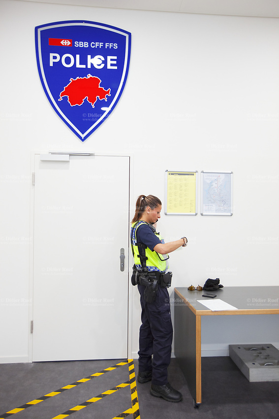 Switzerland. Canton Ticino. Bellinzona. Railway station. A police officer from TPO (Transport Police) inside the police station. The policewoman speaks on her mobile phone and checks the identity of a person who was arrested without any valid ticket in the train. On the wall, the coat of arms of the TPO (Transport Police) and a red drawing with a map of Switzerland. TPO (Transport Police) is the Swiss Federal Railways Police. Swiss Federal Railways (German: Schweizerische Bundesbahnen (SBB), French: Chemins de fer fédéraux suisses (CFF), Italian: Ferrovie federali svizzere (FFS)) is the national railway company of Switzerland. It is usually referred to by the initials of its German, French and Italian names, as SBB CFF FFS. A police station or station house is a building which serves for police officers. The building contains temporary holding cells and interview/interrogation rooms 12.06.2017 © 2017 Didier Ruef