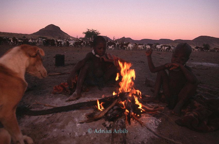 Himba children sit around a fire,  Northern Namibia.