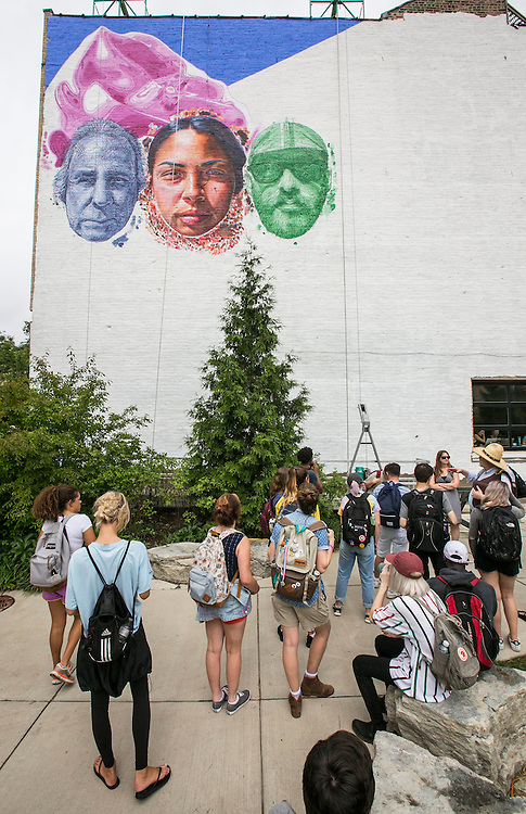 """Brother Mark Elder and his group of freshmen students stumble upon a newly-created mural while walking on the """"The 606"""" Tuesday, Aug. 30, 2016, in Chicago's West Town neighborhood. Elder and his students were in search of public art and murals as part of their Discover Chicago class during Immersion Week 2016. (DePaul University/Jamie Moncrief)"""