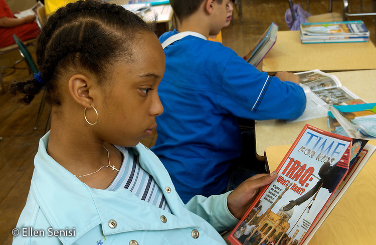 MR / Schenectady, NY.Yates Arts in Education Magnet School / urban public elementary school / Grade 5.Girl (11, African-American) reads current events magazine written for fifth grade students.  Lead article is about post-war Iraq. (Current events is component of 5th grade social studies curriculum)..MR: AD-g5a Bla6..© Ellen B. Senisi