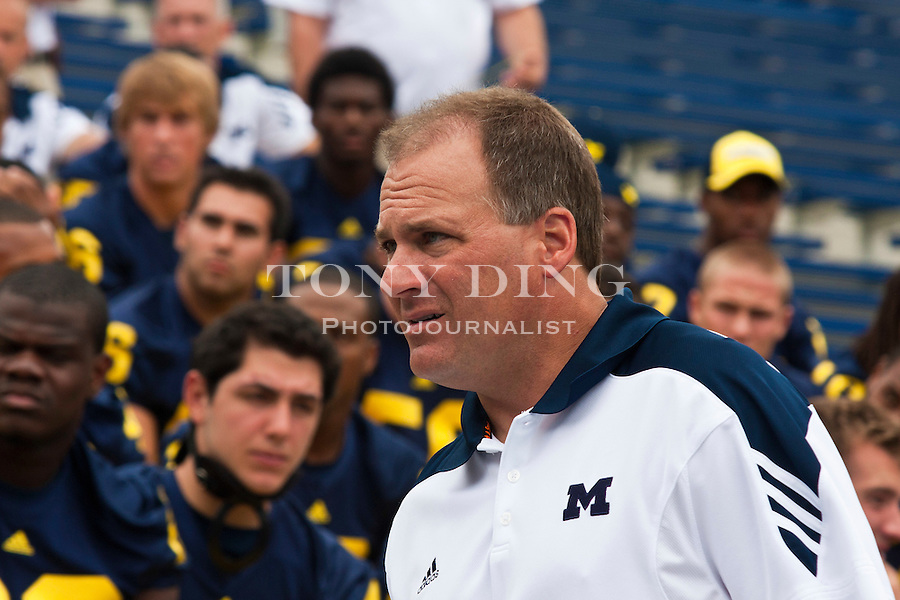 Michigan head coach Rich Rodriguez walks in front of his players after a team photo, at the annual NCAA college football media day, Sunday, Aug. 22, 2010, in Ann Arbor, Mich. (AP Photo/Tony Ding)
