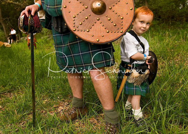 A young red headed boy stands next to his father at the Loch Norman games in Huntersville, NC.