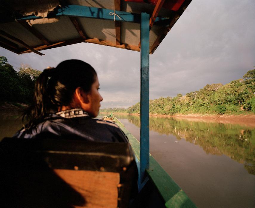 Peruvian woman rides in canoe on the Tambopata River, Tambopata Nature Reserve, Peru, South America