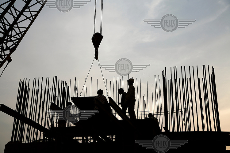 Workers on the construction site of a new elevated highway.