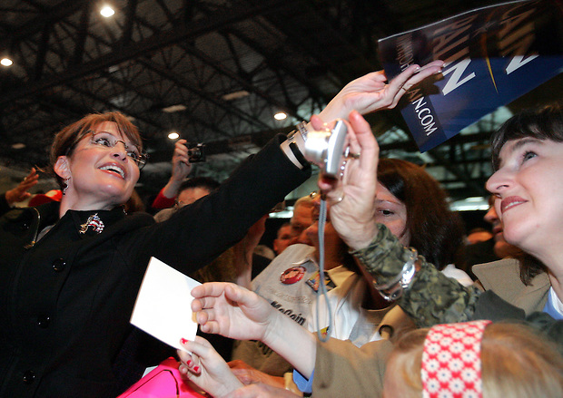 Republican vice presidential candidate, Alaska Gov. Sarah Palin reaches to return an autographed campaign sign during a rally in Des Moines, Iowa Saturday, October 25, 2008.