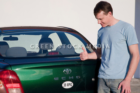 Man holding thumbs up after attaching a 38 miles per gallon fuel efficiency bumper sticker on Toyota Echo car. Sticker from MPG Stickers (mpgstickers.com), a grassroots, nonprofit campaign which aims to accelerate the adoption of fuel efficient vehicles in the United States. California, USA. Property released from mpgstickers.com.