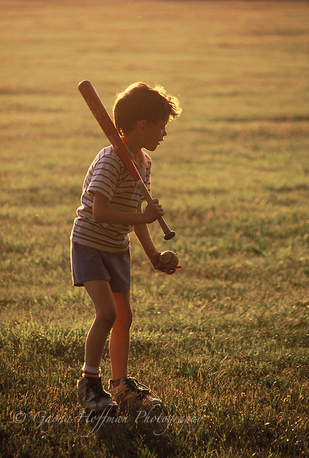 Young boy playing with ball and bat.