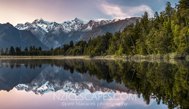 Winter pink, dawn over Mt. Cook and Mt. Tasman of Southern Alps, reflecting in Lake Matheson, Westland Tai Poutini National Park, West Coast, UNESCO World Heritage Area, South Westland, New Zealand, NZ