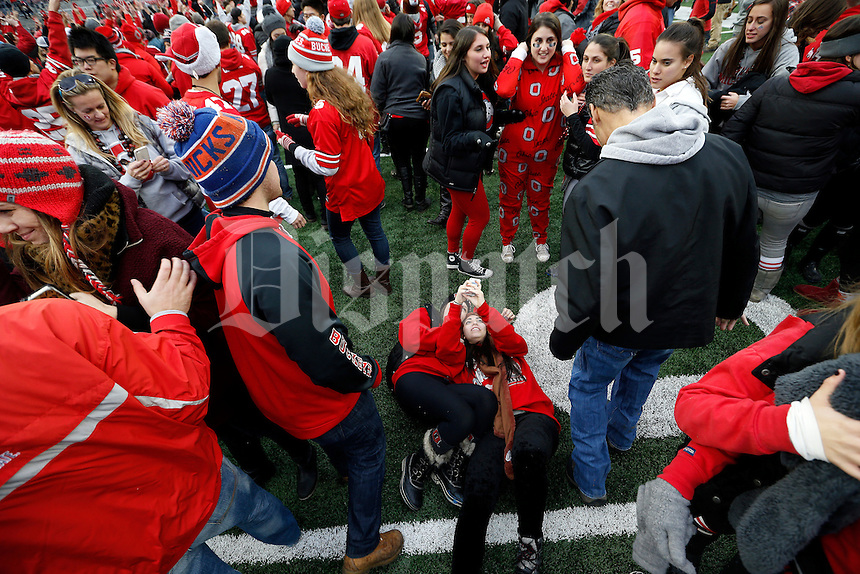 Ohio State seniors Hannah Guttman, left, and Nomi Chayot take a selfie at mid-field following the NCAA football game against the Michigan Wolverines at Ohio Stadium on Nov. 29, 2014. The Buckeyes won 42-28. (Adam Cairns / The Columbus Dispatch)