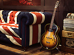 Vintage acoustic Gibson guitar on a stand at a sofa with Union Jack pattern on it