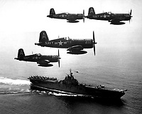 F4U's (Corsairs) returning from a combat mission over North Korea circle the USS Boxer as they wait for planes in the next strike to be launched from her flight deck - a helicopter hovers above the ship.  September 4, 1951. (Navy)<br /> NARA FILE #:  080-G-433002<br /> WAR & CONFLICT BOOK #:  1414