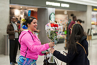 A woman is given a bouquet of flowers as she arrives from Dubai after a 14-hour flight on Emirates flight 231, at the international terminal at Dulles International Airport in Dulles, Va., Monday, March16, 2020. Some people are taking the precaution of wearing face masks as they arrive to be greeted by family and or friends. Credit: Rod Lamkey / CNP/AdMedia