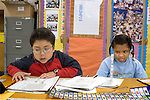 Oakland CA 2nd graders practicing reading fluency--one reads, one times words per minute with egg timer