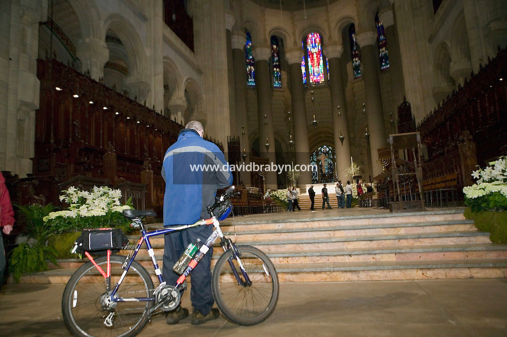 A cyclist leaves the Cathedral of St John the Divine in New York City, USA, after the annual blessing of the bicycles, 22 April 2006. Several dozens cyclists, professional and recreational, and a few roller skaters attended the ceremony during which prayers were said for those who died in cycling accidents this year and to ask for a safe season.<br />