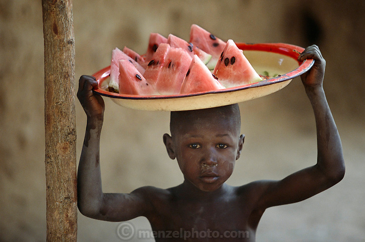 On a warm Saturday afternoon, a young boy with fresh watermelon slices uses the tray for shade as he walks through Kouakourou, Mali, seeking buyers. He pauses by the outdoor barbershop where Soumana Natomo and a group of men are watching a documentary about a Los Angeles SWAT team. Their black-and-white TV is powered by a car battery charged by a solar panel on the roof of the small pharmacy next door. Hungry Planet: What the World Eats (p. 217). This image is featured alongside the Natomo family images in Hungry Planet: What the World Eats.