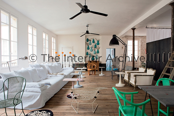 General view of the loft's open plan living space furnished with a long white linen sofa and an eclectic assortment of chairs