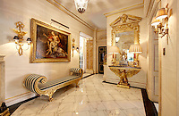 An opulent ante-room with a gilded cornice and a marble floor.  Two lamps stand on a gilded eagle table with an ornate mirror above. A painting hangs above an empire style seat with striped upholstery.