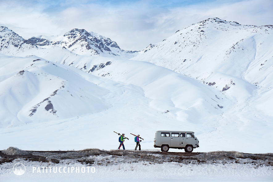 Two ski tourers approaching their vehicle, a Russian made UAZ 452, while traveling in Kyrgyzstan